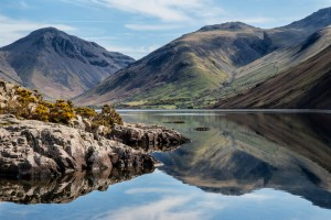 Stunning landscape of Wast Water and Lake District Peaks on Summer day reflected in perfect lake